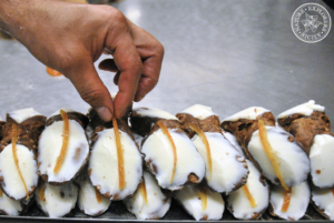 Taste fresh cannoli siciliani in the kitchen of a local bar-pastry shop